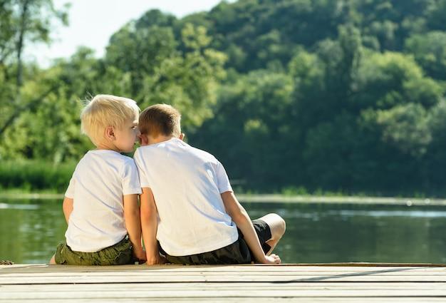 Petit garçon chuchote à l'autre oreille, assis sur la rive de la rivière.