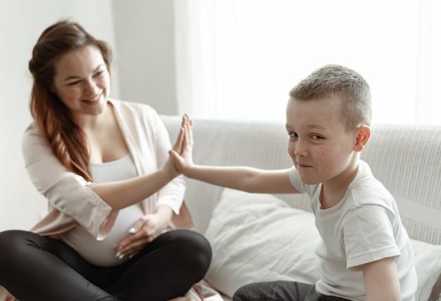 Petit garçon de cinq ans à la maman enceinte assise sur le canapé à la maison.