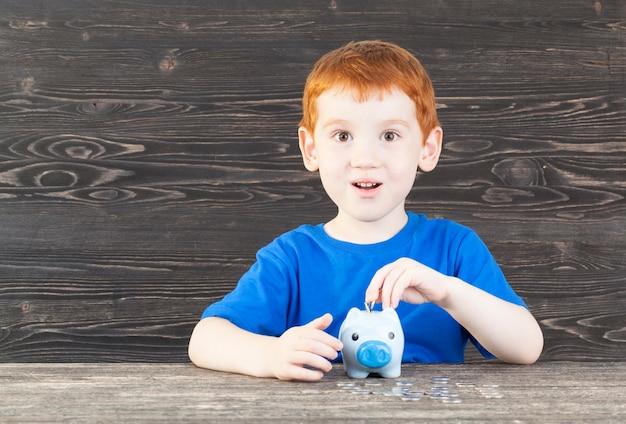 Un petit garçon de cinq ans pose dans sa tirelire sous la forme d'un cochon une pièce de monnaie de couleur argentée, un gros plan dans la pièce