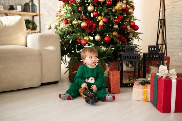 Petit garçon avec des coffrets cadeaux et arbre de noël