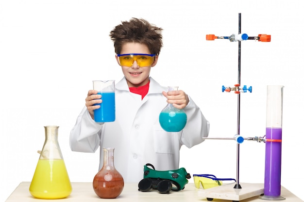 Petit garçon comme chimiste faisant l'expérience avec un fluide chimique en laboratoire