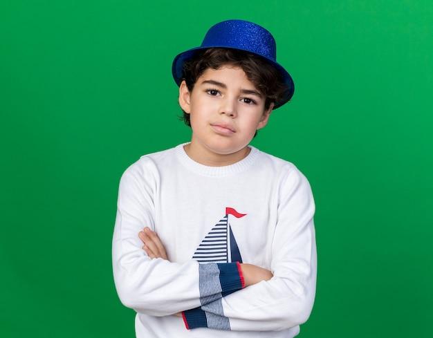 Petit garçon confiant portant un chapeau de fête bleu traversant les mains isolées sur un mur vert