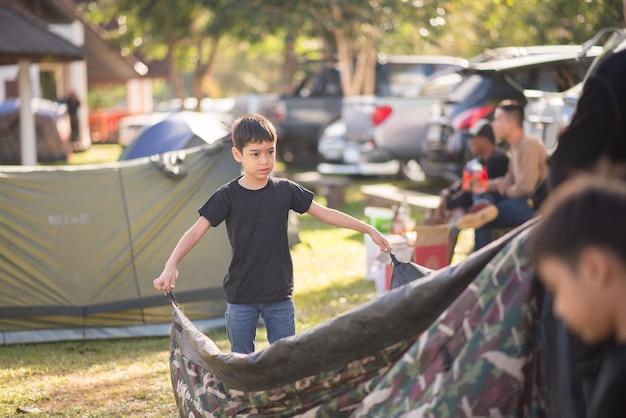 Petit garçon construit une tente pour le camping avec l'heure d'été des vacances en famille