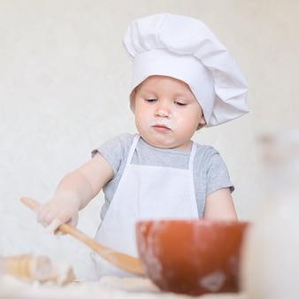 Le petit garçon en costume de cuisinier sculpte la pâte petit marmiton prépare le dîner en costume de chef