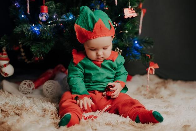 Petit garçon en costume elf assis sous un sapin de noël