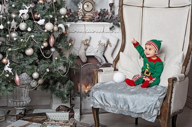 Petit garçon en costume elfe assis sur la chaise à l'intérieur de la maison au coin du feu et attendant le père noël