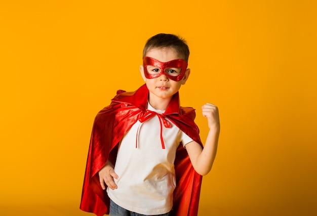 Petit garçon en costume de héros sur une surface jaune avec un espace pour le texte