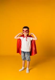 Petit garçon en costume de héros avec une surface jaune avec un espace pour le texte