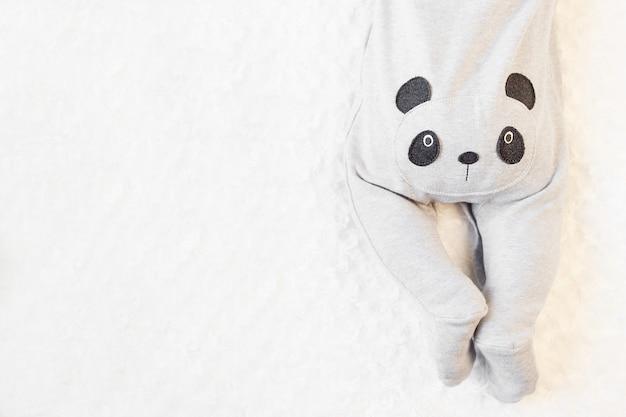 Petit garçon en costume de panda se trouve sur le lit.