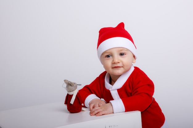 Petit garçon en costume de père noël assis sur un cube blanc sur fond blanc