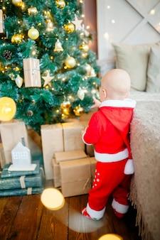 Petit garçon avec costume de père noël décore un arbre de noël. noël