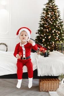 Un petit garçon en costume de père noël gonfle des bulles de savon à l'intérieur décoré pour noël