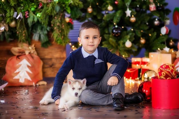 Petit garçon à côté de l'arbre de noël