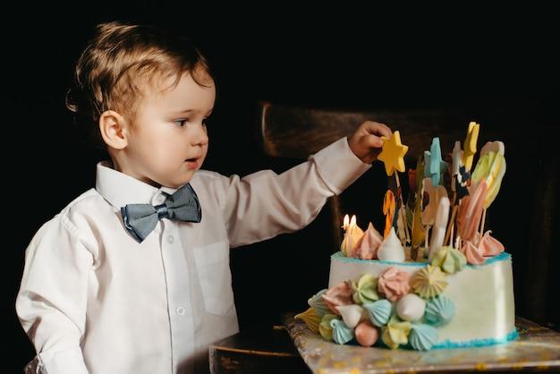 Un petit garçon à côté d'un gâteau pour son anniversaire