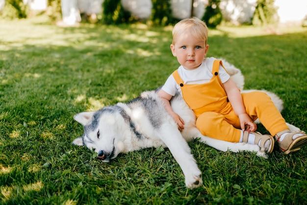 Un petit garçon couché avec le chien sur l'herbe