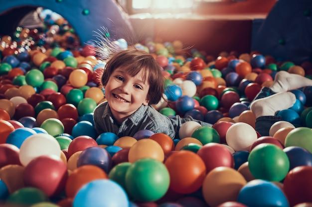 Petit garçon couché dans la piscine pleine de balles colorées