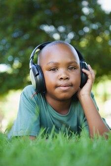 Petit garçon couché sur l'herbe en écoutant de la musique en souriant à la caméra sur une journée ensoleillée