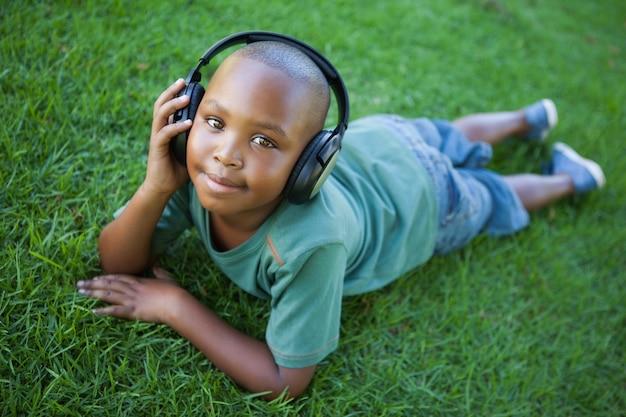 Petit garçon couché sur l'herbe en écoutant de la musique en souriant à la caméra