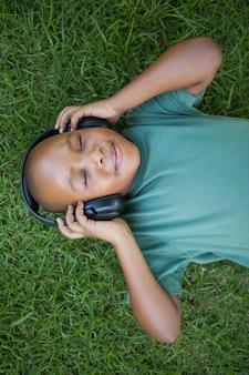 Petit garçon couché sur l'herbe en écoutant de la musique avec les yeux fermés