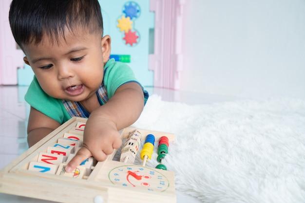 Petit garçon couché et jouant à un jouet en bois