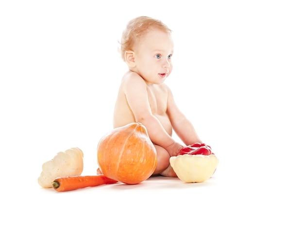 Petit garçon en couche avec des légumes