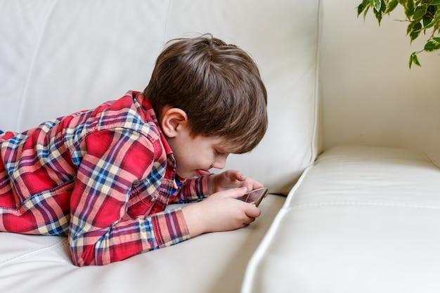 Petit garçon couché sur le lit jouer un téléphone intelligent