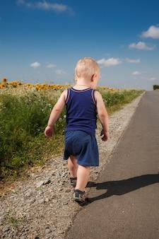 Petit garçon en cours d'exécution sur le bord de la route goudronnée