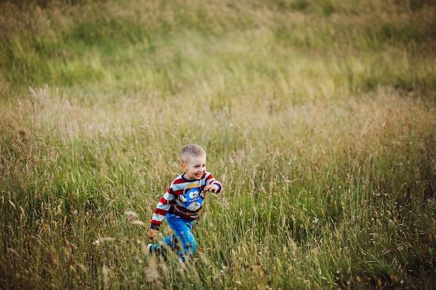 Petit garçon court sur le champ vert
