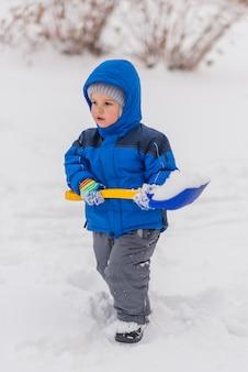 Un petit garçon creuse la neige avec une pelle en hiver.