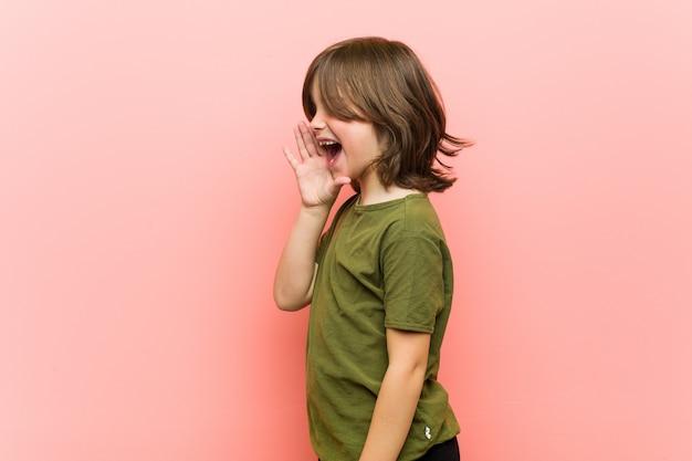 Petit garçon en criant et en tenant la paume près de la bouche ouverte.