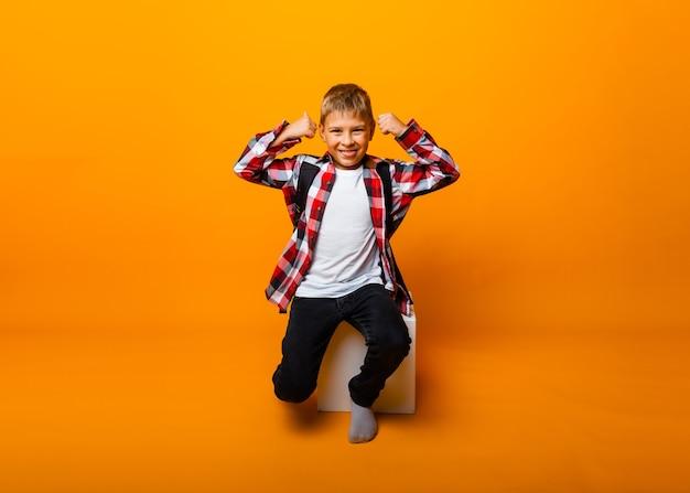 Le petit garçon crie, se tord et montre la classe sur fond jaune