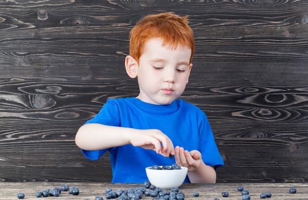 Petit garçon cueillette des bleuets mûrs dans une assiette dans la cuisine, des couleurs sombres à l'intérieur