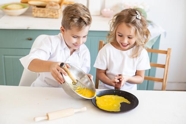 Petit garçon cuisiner avec sa sœur dans la cuisine