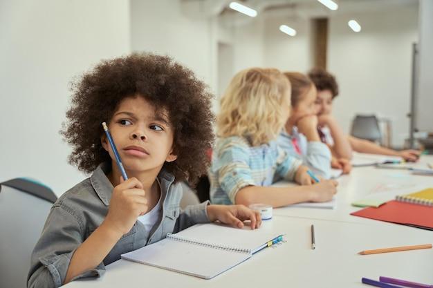 Petit garçon curieux regardant loin pendant la leçon les enfants étudient et prennent des notes assis ensemble à