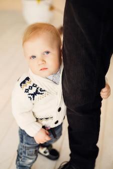 Un petit garçon dans de beaux vêtements tient la jambe de son père