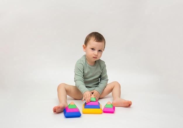 Petit garçon dans un body vert joue avec une pyramide colorée sur fond blanc