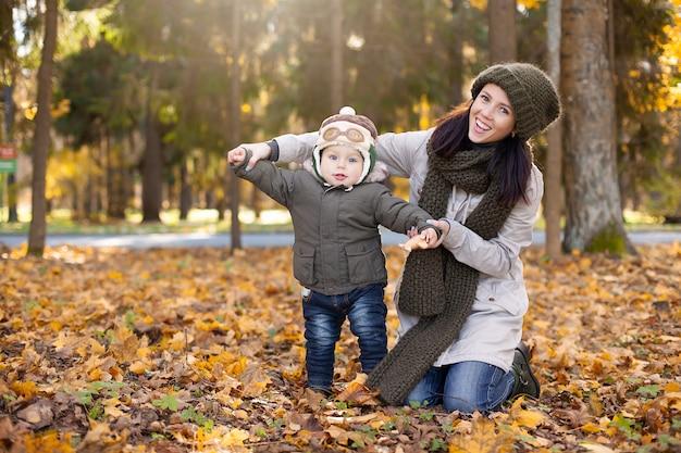 Petit garçon dans la casquette de pilote debout avec sa mère et montrant des ailes, un feuillage jaune et orange autour de lui. l'automne