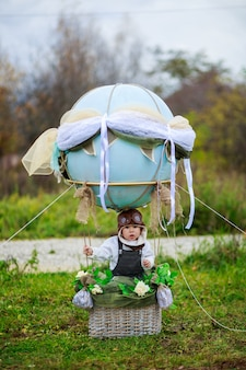 Un petit garçon dans un chapeau d'aviateur est assis dans un panier d'un ballon jouet dans un champ.