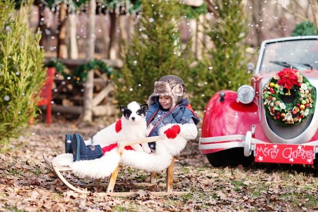 Un petit garçon dans un chapeau de bouchons d'oreille et mitaines rouges est assis dans un traîneau avec un chiot husky