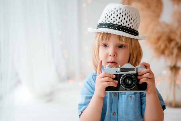 Petit garçon dans un chapeau d'été tenant un appareil photo