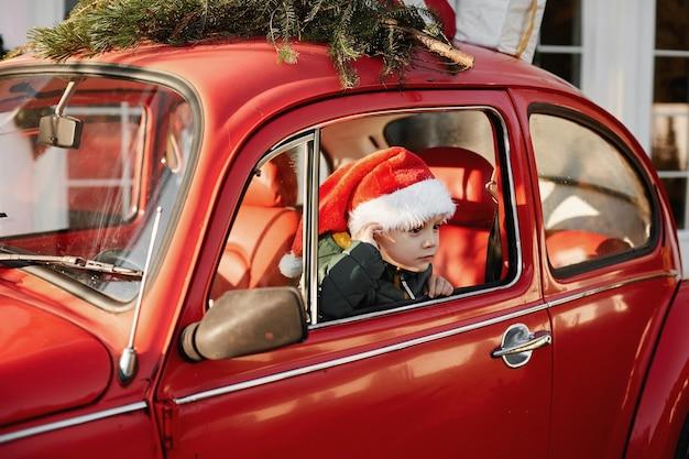 Un petit garçon dans un chapeau de père noël posant dans une voiture rétro rouge avec un arbre de noël sur le toit