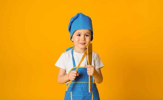 Petit garçon dans un costume de chef se dresse avec des cuillères en bois sur une surface jaune avec un espace pour le texte