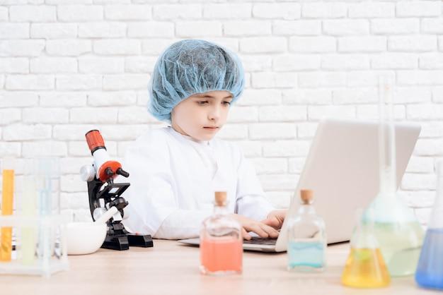 Un petit garçon dans le costume d'un scientifique.