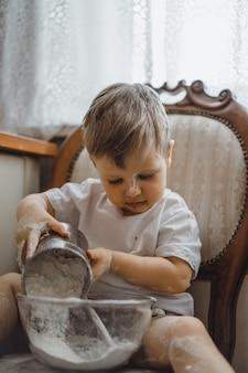 Petit garçon dans la cuisine aide maman à cuisiner. l'enfant est impliqué dans la cuisine.