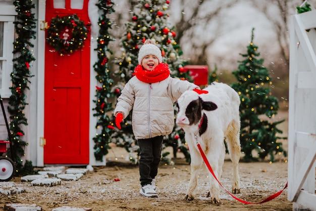 Un petit garçon dans un foulard rouge embrasse un petit taureau noir et blanc