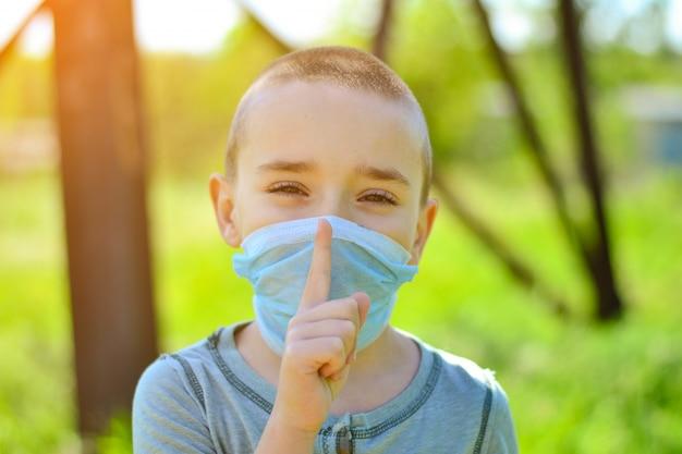 Un petit garçon dans un masque médical.