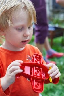 Un petit garçon dans un polo orange tient un avion jouet
