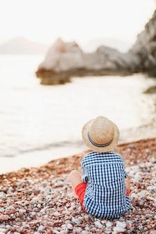 Petit garçon dans un short rouge chemise à carreaux et un chapeau de paille panama est assis sur une plage de galets et regarde