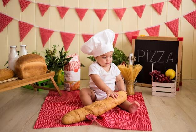 Un petit garçon dans une toque blanche tient un pain