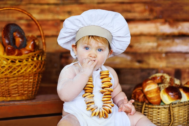 Petit garçon dans une toque et un tablier avec un tas de bagels autour du cou se trouve dans le contexte des produits de boulangerie dans une boulangerie